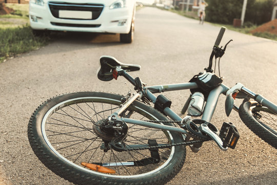 a close-up of a bicycle caught under the wheels of a car. accident on the road, accident, traffic rules