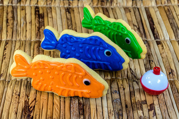 fish cookies with red and white fishing bobber on bamboo mat