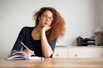 female student sitting at desk and writing notes in book