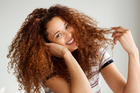 happy young woman with curly hair smiling against white background