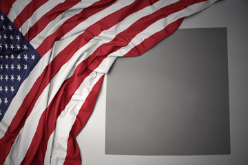 waving national flag of united states of america on a gray colorado state map background.
