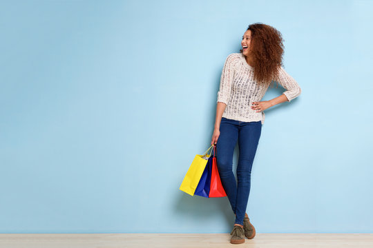 Full body young woman laughing with shopping bags against blue wall