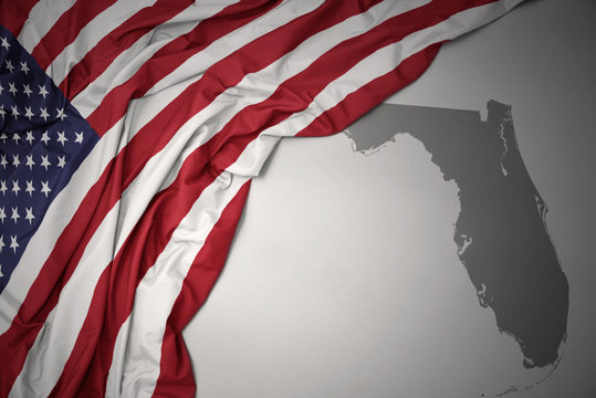 waving national flag of united states of america on a gray florida state map background.