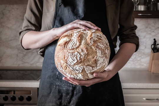 Hands holding big loaf of white bread. Female in black apron in home kitchen background with wheat bread