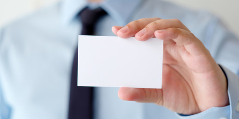 Businessman hand holding blank white business card with copy space for text, business mock up background concept