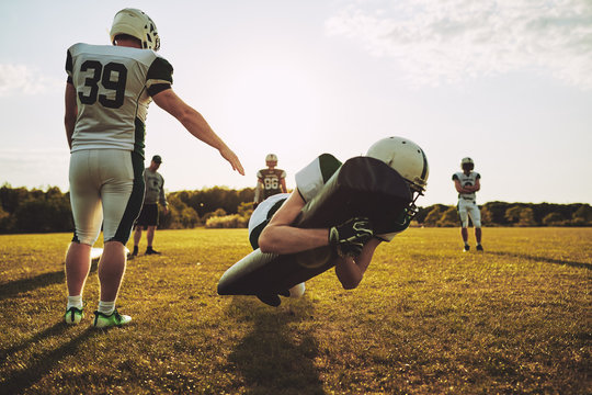 American football players practicing tackles on a football field
