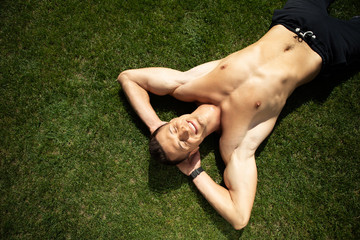 Top view of joyful shirtless man lying on grass and grinning. He is closing eyes and putting arms under head. Male is enjoying rest in open air during sunny warm day