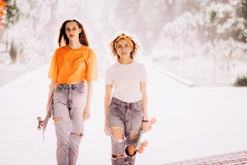 Two beautiful young hippie woman model in summer white hipster clothes posing in the street