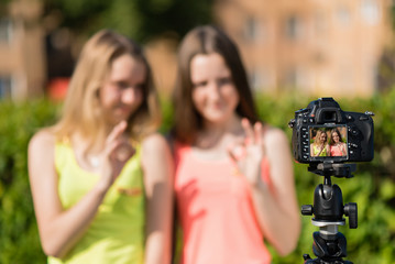two teenage girls are recording video on the camera. Summer in nature. With gestures of hands shows Okay. Free space for text. The camera is on tripod.