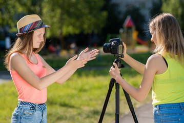 Two girls in the nature. Record a video message on the Internet. In the city after school. Camera with tripod. Happy smiling gestures with hands.
