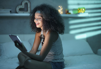 Hispanic Girl Watching Film With Tablet And Laughing