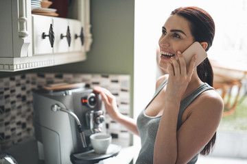 Nice to hear you. Smiling beautiful woman standing by coffee machine and preparing hot drink. She is holding mobile and talking with joy while waiting