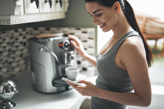 Side view of smiling attractive woman standing by coffee machine with smartphone in hands. She is chatting online with delight