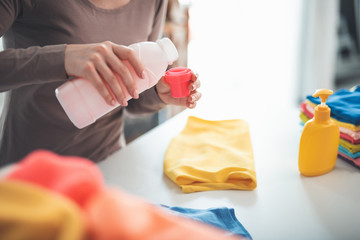 Close up of female hands pouring detergent into bottle lid. She is standing at white table with folded clothes and can of soap nearby