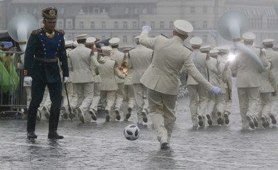 A member of the Guard of Honour of the Presidential Regiment plays with a ball with a conductor of the Presidential Band during the Changing of the Guard ceremony in Red Square in Moscow