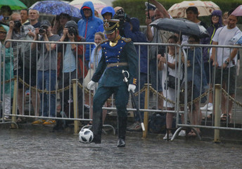 A member of the Guard of Honour of the Presidential Regiment plays with a ball during the Changing of the Guard ceremony in Red Square in Moscow