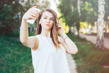 young beautiful woman, teenager, making selfie in park