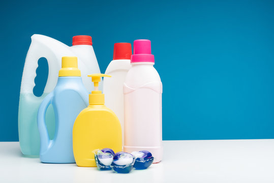 Close up of washing capsules lying together with different washing liquids, soap, softener and bleach. Copy space in right side