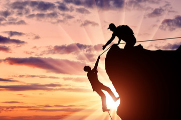 Silhouette of a climber who helps to climb the top of a man, throws him a rope and holds out his hand.