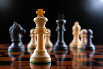 Chess pieces on a chessboard table and a chess piece of the king on a black background