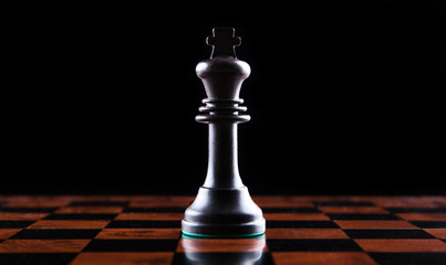 chess piece of a black king on a chessboard on a black background