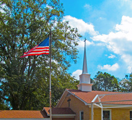 American flag against the blue sky, green tree and church cross.