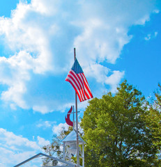 American flag against the blue sky, green tree and church cross. Traditional symbol of America in a bright sunny summer day in the Edom, near Tyler in Texas.