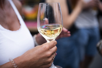 Hands holding a white wine glass