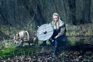 Scandinavian northern viking with wolf, ax and shield in hand looking threateningly. Northern warrior woman in forest in war clothes with fur collar and war makeup.