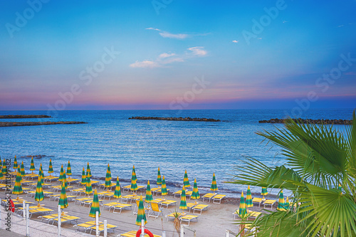 Beach Umbrellas And Sunbeds On The Sea Beach At Sunset Rows