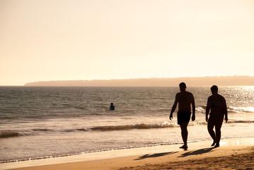 Couple walking on sunset beach