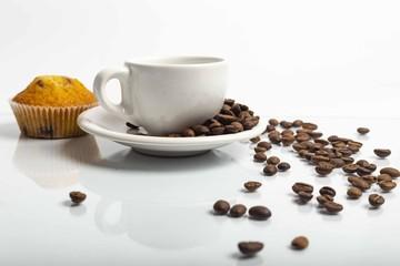 Tazza di caffè bianca con chicchi con un leggero riflesso