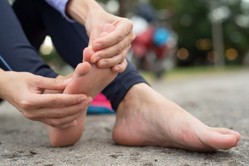 woman feeling pain in her foot during sport outdoor