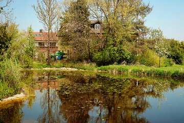 Bavarian coutryside, idyllic pond in spring with house and wood reflection