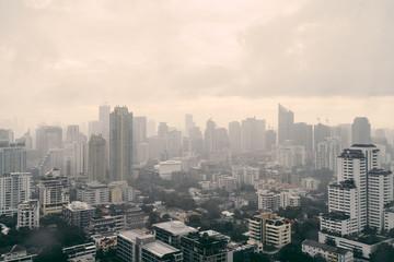 Rain over Bangkok: Cityscape behind the window glass with rain drops.