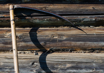 Garden tool - scythe. Wall of the rural house made from wooden logs