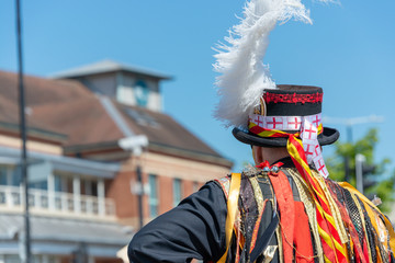 morris dancer with white feather plume in a top hat with England flags attached