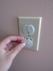 A person inserting a baby proof safety outlet cover into an American outlet