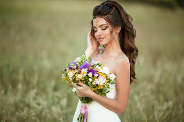 Beautiful young bride is wearing teak with fashion bouquet of wildflowers in yellow field, nature wedding concept