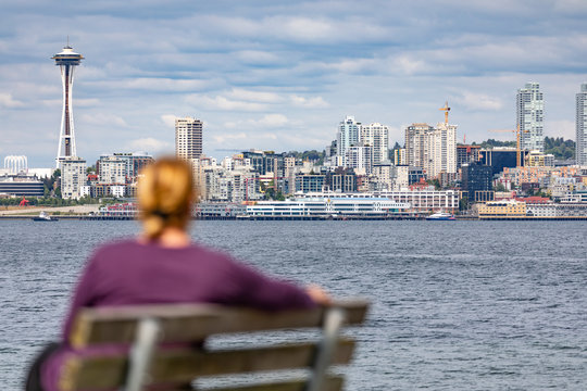 Woman Sitting on Bench Looking At The Seattle, Washington Skyline