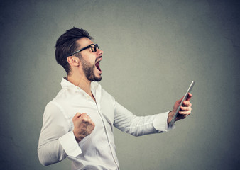 Cheerful hipster man holding tablet and fist up while screaming with happiness