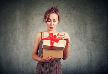 Excited woman opening gift box