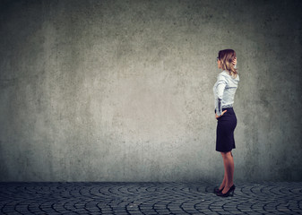 Woman standing against wall obstacle