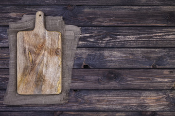 Old cutting board on dark wooden table. Top view. Copy space