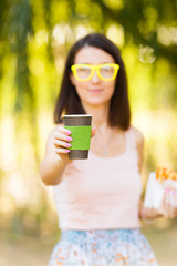 hipster girl in yellow glasses is holding coffee in a paper cup