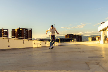Adult guy having fun with skateboard on the rooftop. Young and careless having fun concept.