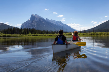 Couple adventurous friends are canoeing in a lake surrounded by the Canadian Mountains. Taken in Vermilion Lakes, Banff, Alberta, Canada.