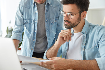 Creative male employees collaborate together on common project, study business documents, work on modern electronic device at office desk, connected to wireless internet. People and work concept