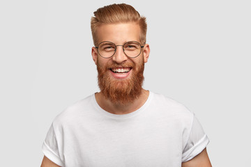 People, youth, positiveness concept. Happy male with long thick ginger beard, has friendly smile, rejoices having day off for his hobby, expresses happiness, stands alone against white wall.