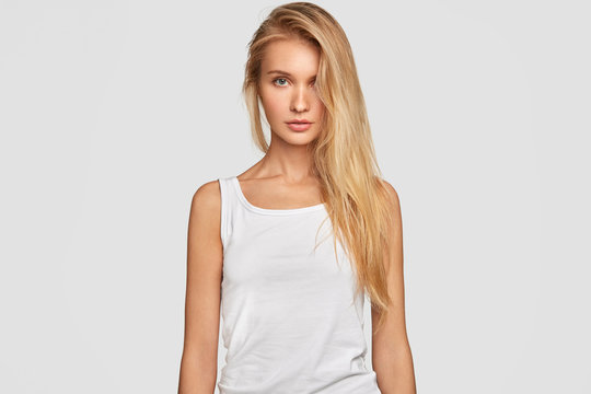 Waist up portrait of sexual young female with blonde long hair combed on one side, wears oversized casual white t shirt, shows perfect figure, has healthy pure skin, goes in for sport regularly